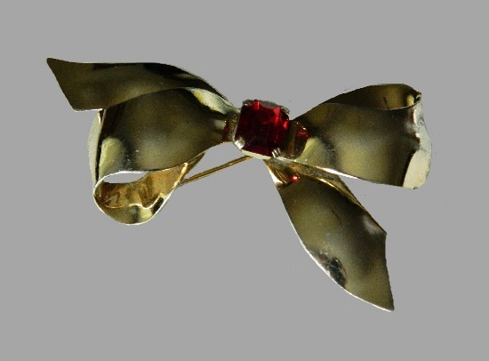 Bow brooch. Gold tone metal, faux ruby