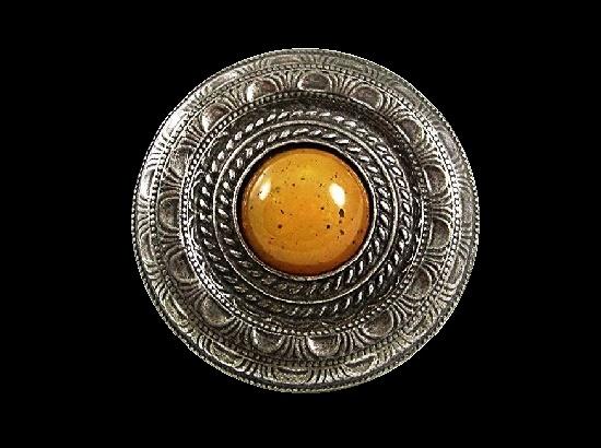 Ornamental round shaped Greek style brooch. Silver tone metal, carmel glass cabochon
