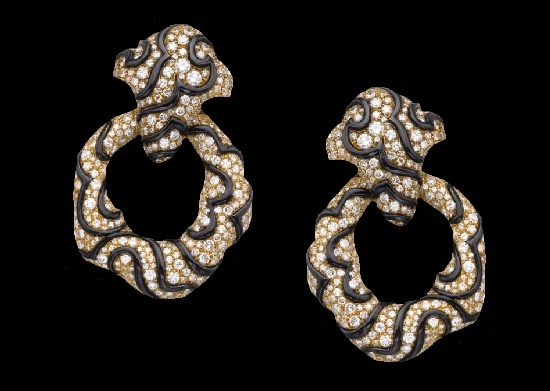 Scroll and wave motif earclips. Pavé-set with brilliant-cut diamonds. Detachable hoop, reversed may be worn as a brooch. 1987