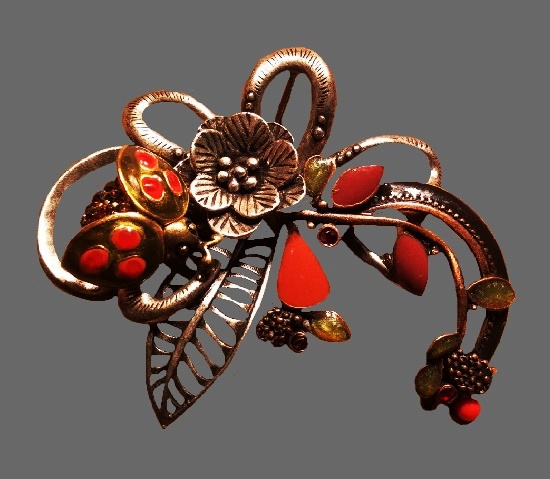 Floral motif brooch. Textured silver tone metal, enamel