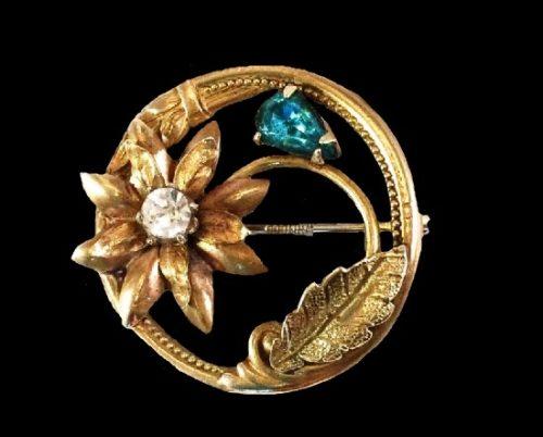 Flower in a circle gold tone brooch, rhinestones