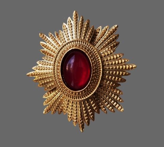 Heraldic design brooch. Gold tone textured metal, lucite scarlet color cabochon. 7 cm. 1980s