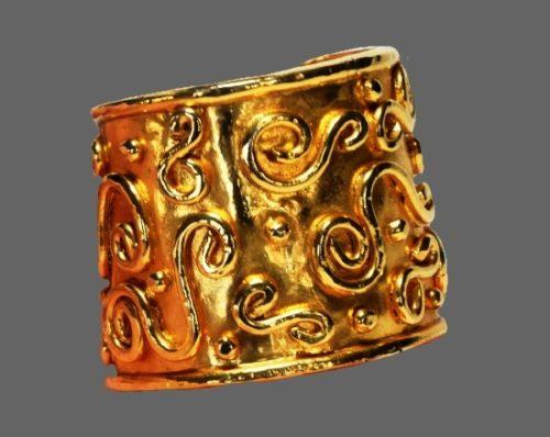 Cuff bracelet. Gold tone metal, ornamental patterns
