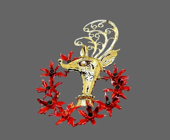 Reindeer with poinsettia wreath brooch. Gold tone, rhinestones, enamel