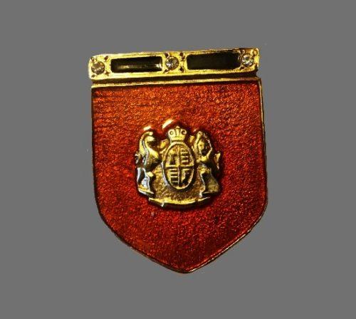 Shield brooch. Orange enamel, rhinestone, gold tone metal