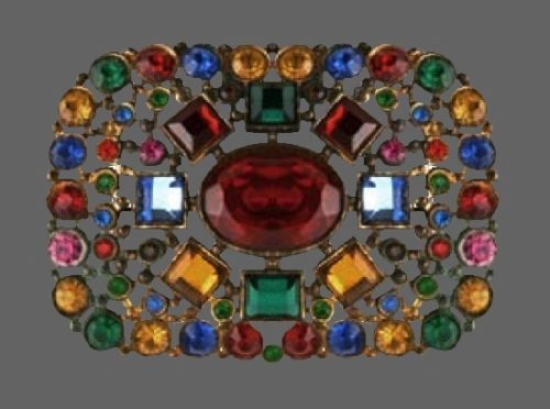 Pin set with numerous crystal rhinestones of various cuts and gemstone colors in a filigree gilt metal backing. Early 1900