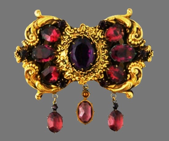 Scrolled cartouche, triple-pendant pin of gilt metal with large, prong-set, Burmese-ruby colored oval cabochons. 1930s