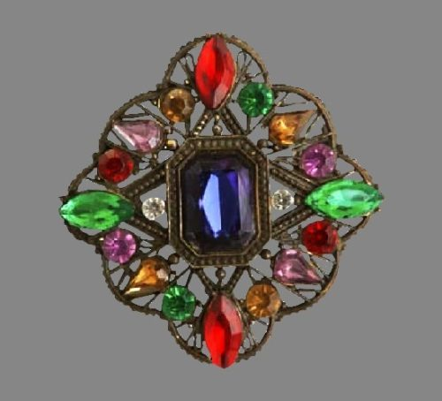 Stylized floral motif pin with ruby, jade, amethyst, and sapphire crystal rhinestones set in a filigree gilt metal backing. 1940s