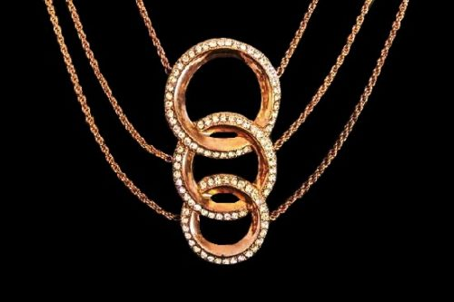 Three rings pendant necklace of gold tone, rhinestones