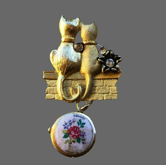 A couple of cats brooch with dangling clock. Gold tone, enamel, rhinestones
