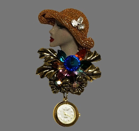 Art Deco Lady floral design brooch with watch. Gold tone metal, mother-of-pearl dial, crystals, rhinestones. 1970s