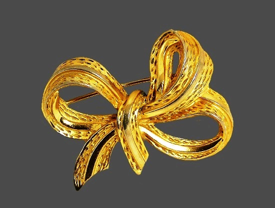 Bow brooch of gold tone. 1980s