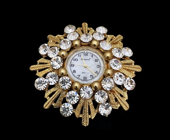 Gold-tone brooch with watch. Gold tone metal, rhinestones, mother of pearl dial. 1970s