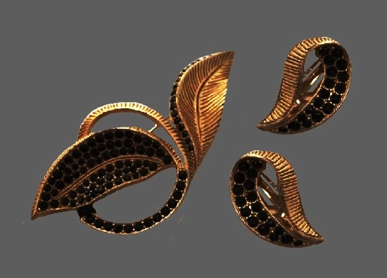 Leaf design brooch and clip on earrings. Black rhinestones, textured gold tone metal alloy. 1960s