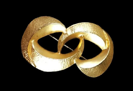 Eternity shaped gold tone brooch. 1980s