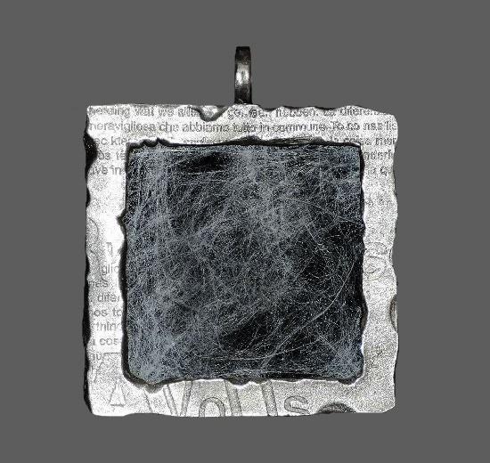 Rectangular frame newsprint pendant. Silver plated metal, cobweb-like fabirc insert. 1990s