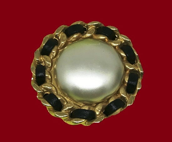Round shaped brooch. Gold plated metal alloy, faux pearl, black leather. 3.8 cm. 1980s