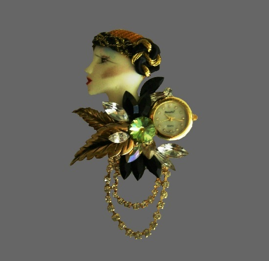 Woman's profile with flowers vintage timepiece. Gold tone alloy, rhinestones, resin. 1970s