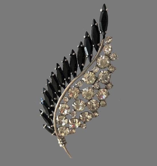 Clear and black rhinestones leaf brooch of silver tone. 1970s