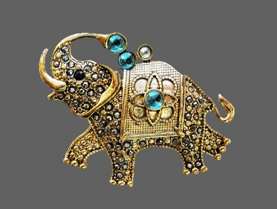 Joyful elephant vintage brooch. Gold tone alloy, crystals, glass cabochons. 5.2 cm. 1960s
