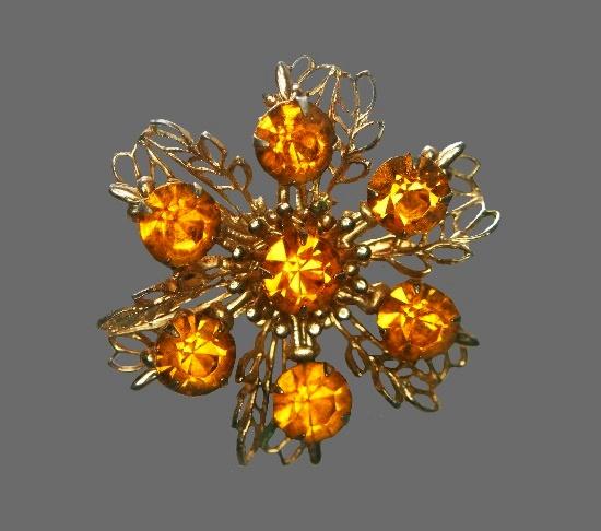 Snowflake brooch pin. Gold tone metal, amber rhinestones