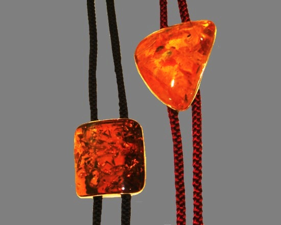 Two amber pendants on a leather cord