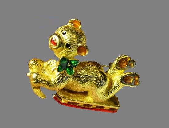 Bear cub on sledges Christmas vintage brooch. Gold tone alloy, enamel. 5 cm. 1960s