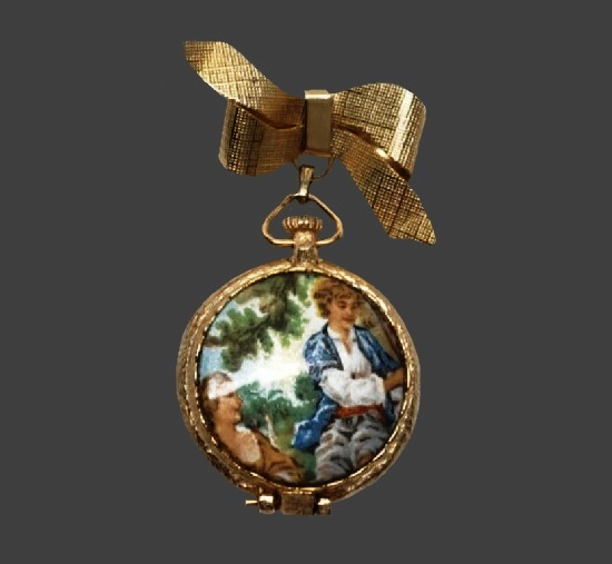 Bow dangling perfume locket brooch with hand painted Victorian scene. Gold plated, 6 cm, 1950s