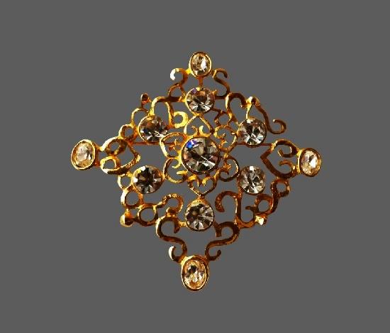 Filigree brooch of gold tone with rhinestones